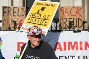 Man at protest holding NO ILF NO LIFE placard