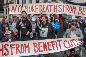 People with banners at a protest which say NO MORE DEATHS FROM BENEFIT CUTS