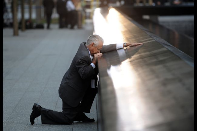 A father mourns at his son's name at the memorial.