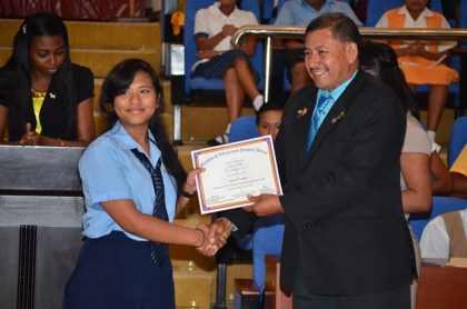 Minister of Indigenous Peoples' Affairs Sydney Allicock handing over the certificate to a student of the Hinterland Scholarship Programme