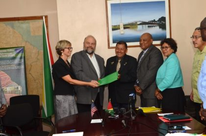 US Ambassador to Guyana Perry Holloway handing over the MoU to Minister of Indigenous Peoples' Affairs Sydney Allicock (center), Minister of Natural Resources Raphael Trotman (second from right), Minister within the Ministry of Indigenous Peoples' Affairs Valerie Garrido-Lowe (right), and Country Director, Peace Corps-Guyana Linda Arbogast (left)