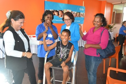 First Lady, Mrs. Sandra Granger (second from right) , Mrs. Tani Austin, Co-Founder of Starkey Hearing Foundation, Dr. Ruth Quaicoe, Head of Audiology in Guyana celebrate with Master Daniel Gobin and his grandmother (first, right) after he was fitted with a hearing device.