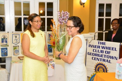 First Lady, Mrs. Sandra Granger smiles as immediate Past President of the Inner Wheel Club of Georgetown Central, Ms. Cherri Peters-Grant (first left) presents her with a bouquet of orchids in appreciation for her attendance at the induction ceremony.
