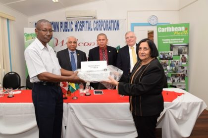Pamela Harakh, cofounder of Caribbean North Charities Foundation Guyana, handing over the equipment to GPHC's Chief Executive Officer (CEO), Allan Johnson.  Minister of Public Health, Dr. George Norton and Canadian High Commissioner to Guyana, Pierre Giroux look on.