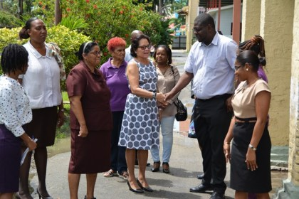 First Lady, Mrs. Sandra Granger chats with Mr. Whentworth Tanner, Director of Social Services at the Ministry of Social Protection, while care-givers, matrons and other persons look on.