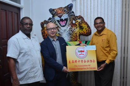 Representative of the Association of Chinese Enterprises in Guyana, Kevin Lue (center) presents $500,000 cheque to Guyana Tourism Authority's Director, Indranauth Haralsingh (right) and Permanent Secretary of the Ministry of Public Telecommunications, Derrick Cummings (left)