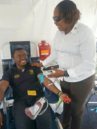 Minister within the Ministry of Public Infrastructure, Annette Ferguson (right), interacts with a member of staff during the ministry's recent blood drive