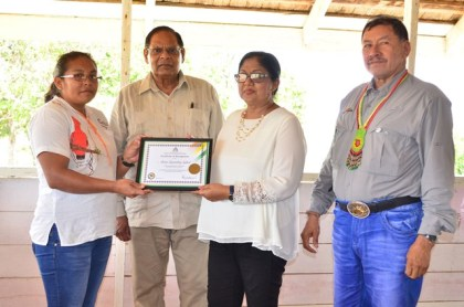 A teacher of the Annai Secondary School receives the OPM Certificate of Recognition from Mrs Sita Nagamootoo while Prime Minister Moses Nagamootoo and VP Sydney Allicock look on.