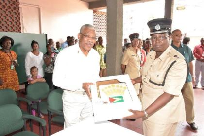 President David Granger receives a cake, with the Guyana Flag and the Presidential Standard symbol from a representative from the Guyana Police Force