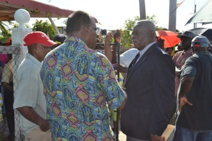 Flood-affected rice farmers explain their plight to Minister of Citizenship, Mr. Winston Felix at the Community Development Centre at Union Village