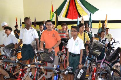 Minister of Social Cohesion, Ms. Amna Ally and some of the Region Four recipients of bicycles and backpacks interact after the ceremony