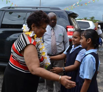 Two students greet Minister of Social Cohesion, Ms. Amna Ally at the Blairmont Primary School
