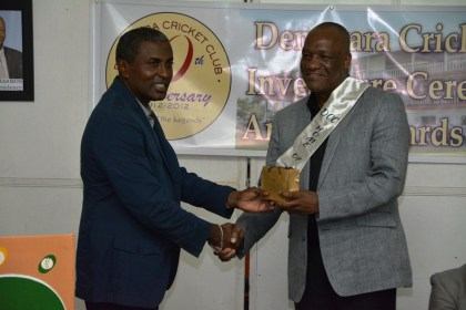 Minister Harmon receiving a token of appreciation from President of the DCC, Mr. Alfred Mentore