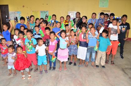 Prime Minister Moses Nagamootoo and team pose with children of Fairview
