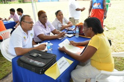 Officials from the Minister of Social Protection listening attentively to the concerns of this resident at the Meet the Public event held in Linden today.