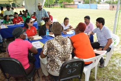 Staffers of the Ministry of Communities in the foreground and the Guyana Lands and Surveys Commission attending to residents at the Meet the Public event at the Mckenzie Sports Club Ground in Linden, today.