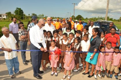 President David Granger helps this little girl cut the ribbon to mark the opening of the Ruby Paved Road, which is 7.7 km long. This project also included a reinforced concrete bridge and culverts