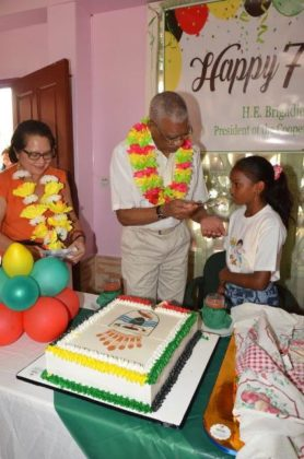 President David Granger sticks his birthday cake with little Rebecca one of the children at the Hope Children's Home, as First Lady, Mrs. Sandra Granger (first, left) looks on.