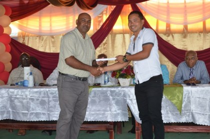 Mayor of Corriverton, Ganesh Gangadin presents a certificate to a graduate of the National Training Programme for Youth Empowerment under the Board of Industrial Training. The training was done at the Upper Corentyne Industrial Training Centre