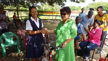 Minister of Social Cohesion Amna Ally presents a bicycle to Josanya Foo one of the top NGSA students of Region Nine