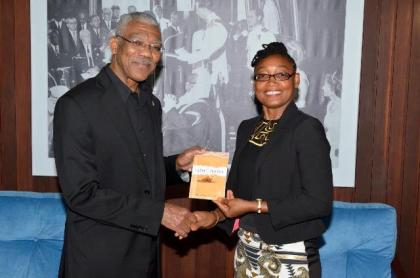 Ms. Marcia Shury hands over a copy of the book to President David Granger, earlier today at the Ministry of the Presidency.