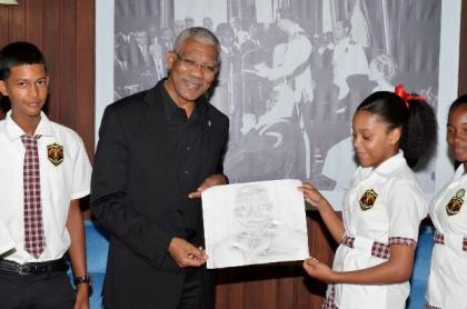 Fourteen years old Hannah Monroe hands over the portrait she drew with charcoal to President David Granger, earlier today at the Ministry of the Presidency.