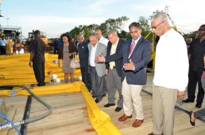 Chief Executive Officer of GAICO Construction and General Services Incorporated, Mr. Komal Singh, explains the operation of this apparatus to President David Granger, at the launch of the Oil Spill Response Services company.