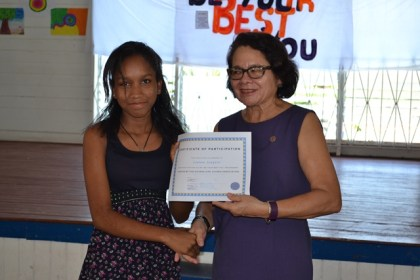 Ms. Leanna Jaoquin accepts her certificates from First Lady, Mrs. Sandra Granger