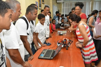 First Lady, Mrs. Sandra Granger takes a closer look at the robot built by these participants.