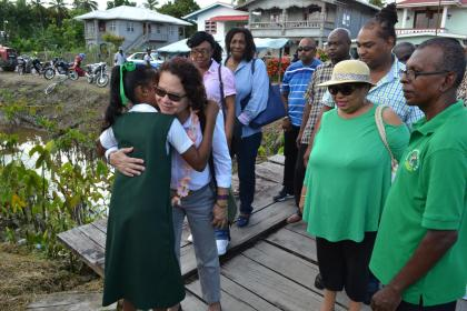 Mrs Granger receives a hug from a student on her arrival at the Arthurville Primary School, in Wakenaam, Essequibo Islands-West Demerara (Region 3)