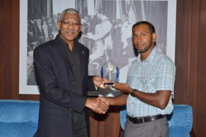President David Granger receives a token from the President of the Guyana Chess Federation, Mr. Irshad Mohamed, who also inducted him as an honorary member of the Federation.