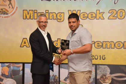 Minister of Business, Mr. Dominic Gaskin, presents the Top Producer Award to the representative of Adamantium Holdings
