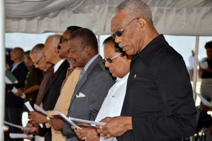 """President David Granger, Prime Minister Moses Nagamootoo, Speaker of the National Assembly, Dr. Barton Scotland participating in the singing of the hymn """"Immortal, invisible, God only wise"""" at the Commemorative Ceremony for the Demerara Revolt 1823."""