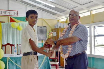 Naresh Jaganand receiving his trophy for his outstanding performance at the National Grade six examinations