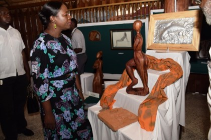 Minister within the Ministry of Education, Department of Culture, Youth and Sport, Nicolette Henry taking a look at one of the sculptures on display at the Burrowes School of Art exhibition