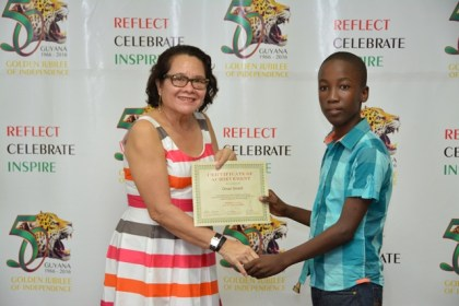 First Lady, Mrs. Sandra Granger presents a Certificate of Achievement to Master Omari Smartt, who graduated from the workshop held at the Friendship Primary School, Friendship, East Coast Demerara.