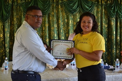 Regional Chairman Mr. Brentnol Ashley presents a certificate to Ms. Nevita Poliah, who said that she intends to use her newly acquired knowledge to open an electronics business.