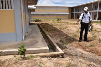 Architect Davendra Doodnauth of Rodrigues Architects Ltd. points out a defective drain during a tour of the Kato Secondary School construction project