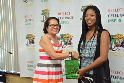 First Lady Mrs. Sandra Granger presents a token of appreciation to Ms. Ima Christian at the graduation ceremony of the Lego Robotics STEM workshop held at the National Sports Resource Centre.