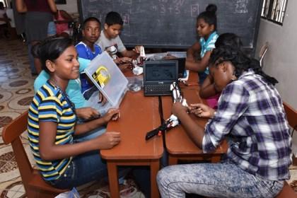Participants f the STEM workshop at Lusignan building a robot