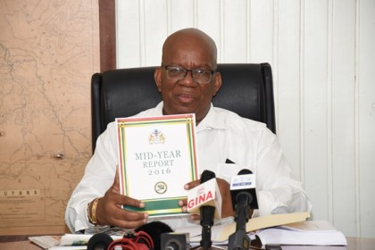 Minister of Finance, Winston Jordan displays a copy of the Midyear report at the Ministry of Finance