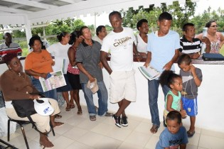 Residents at the meeting in Kimbia with Minister of Social Protection, Volda Lawrence and team