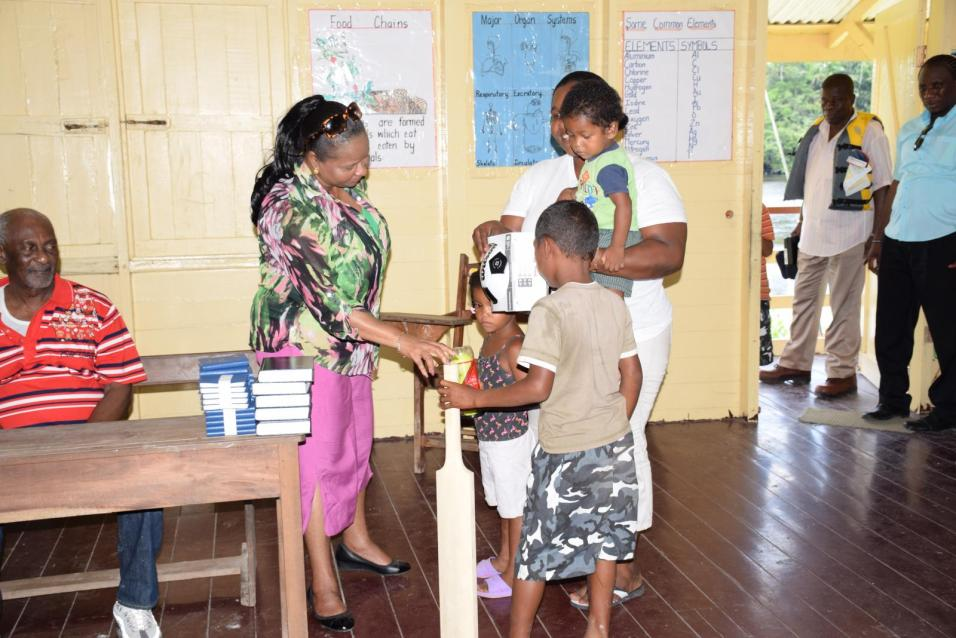 Minister of Social Protection, Volda Lawrence presenting sports gear to a teacher of the Ebini Primary School, Upper Demerara River