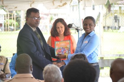 Public Security Minister Khemraj Ramjattan presenting a copy of the Guyana National Road Safety's first ever magazine to a representative of Massy Group of Company. Massy was one of several sponsors that contributed towards the publishing of the magazine.