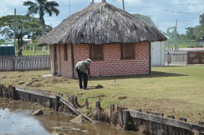 A worker adding some finishing touches on the surroundings of the Heritage village at the Sophia Exhibition complex compound, Georgetown