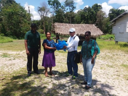 Public Health Minister, Dr. George Norton hands over some of the treated mosquito nets to Kurutuku Resident, Lena Lewis. Also in the photo are Director of Vector Control Services, Dr. Horace Cox (left) and Director of Regional Health Services, Dr. Kay Shako (right)