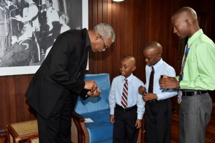 President David Granger giving the three brothers tokens, during their visit to the Ministry of the Presidency.