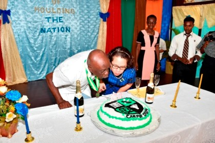 First Lady, Mrs. Sandra Granger sticks the celebratory cake with the oldest member of the alumni present at the ceremony today; Mr.Norman Semple (Class of 1942)