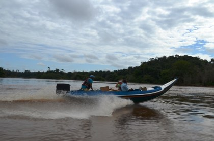 Ministry of Health officials delivering drugs to a riverine community by water transport