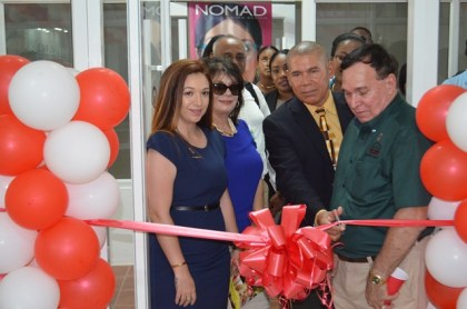 Dr. Shannon Da Silva, BSc. Her parents Barbara and Philip Da Silva watch on as Minister of Public Health Dr. George Norton cuts the ribbon to commission the opening of Da Silva's Optical branch in Parika